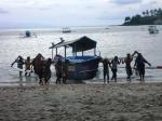 nelayan menggotong perahu
